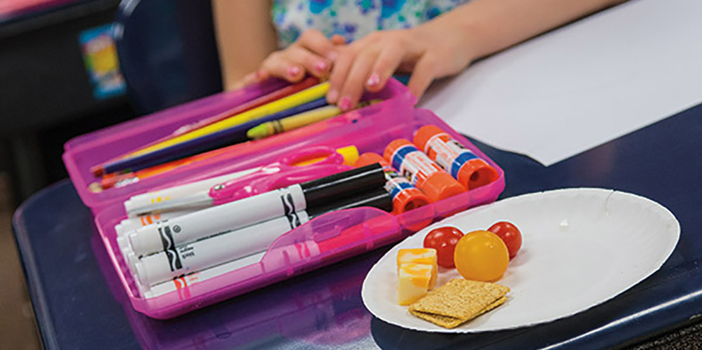 Image of a school student's desk with markers, paper, and a paper plate with a cracker, cheese and grapes.